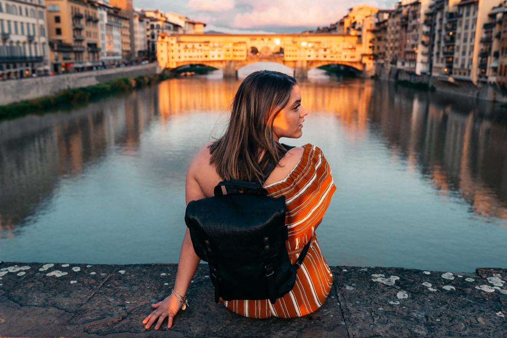 A young woman sits on a slab of concrete with Florence's Ponte Vecchio in the background.